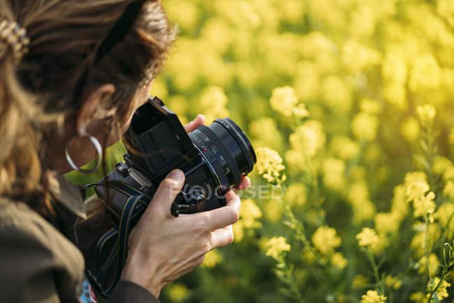 Close-up de mulher com câmera retro tirar foto na natureza com flores amarelas — Fotografia de Stock