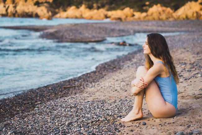 Jovem mulher pensativa em maiô sentado na praia e olhando para a vista — Fotografia de Stock