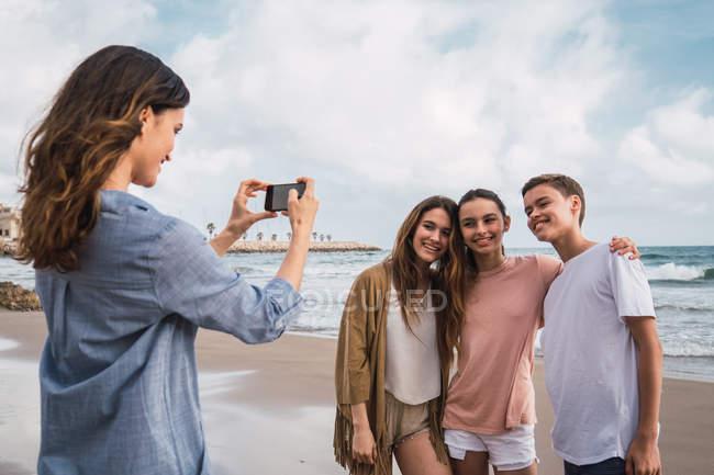 Mulher fotografando crianças com smartphone na praia — Fotografia de Stock