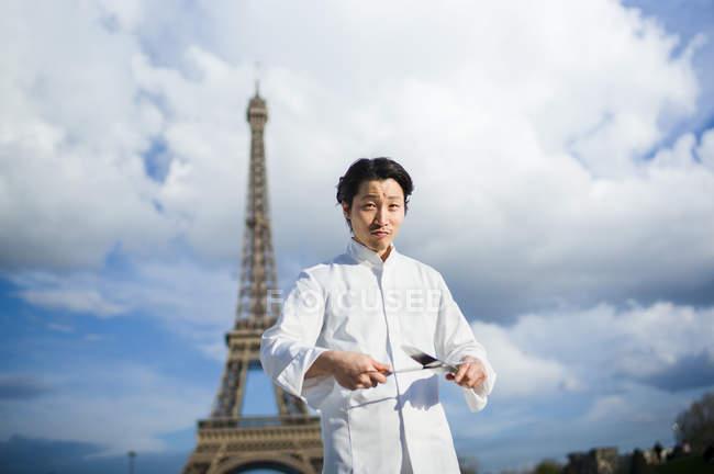 Porträt eines lächelnden japanischen Kochs mit Messern vor dem Eiffelturm in Paris — Stockfoto