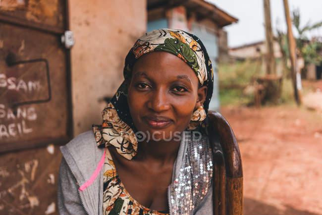 CAMERÚN - ÁFRICA - 5 DE ABRIL DE 2018: Mujer africana adulta sonriente mirando a la cámara mientras está sentada en su casa en la calle del pueblo - foto de stock