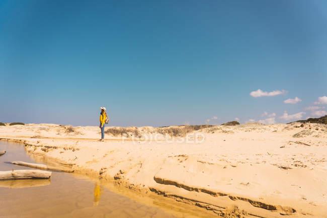 Жінка в капелюсі стоячи на піщаному березі під Синє небо — стокове фото