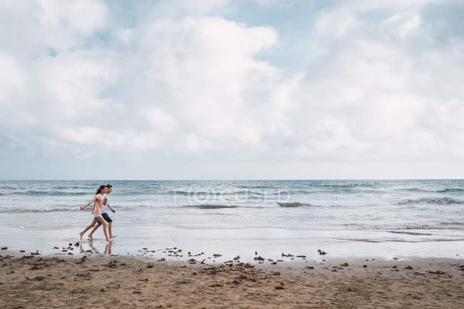 Teen boy and girl walking on beach in summer — Stock Photo