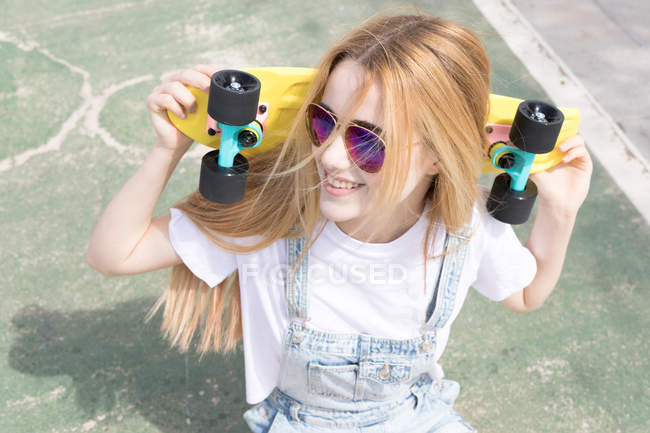 Blonde girl with penny board sitting in skate park — Stock Photo