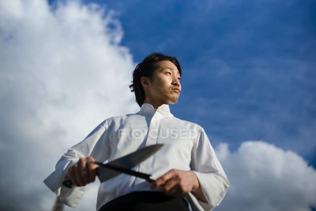 Chef japonés con cuchillos delante del cielo azul con nubes - foto de stock