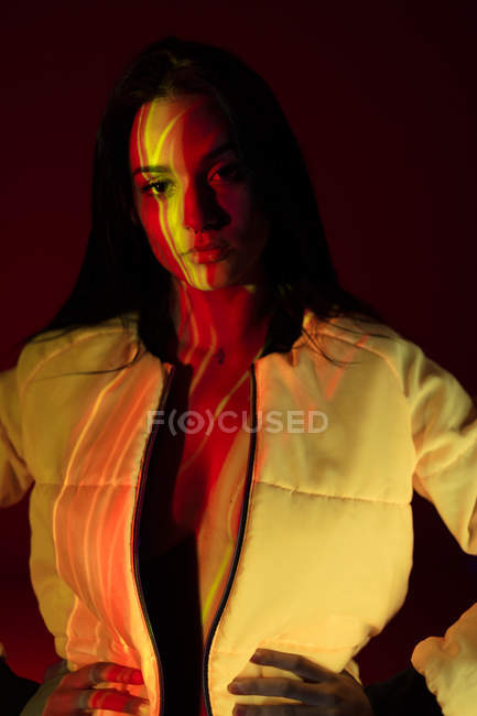 Young woman in white jacket with light stains on face standing with hands on heap — Stock Photo