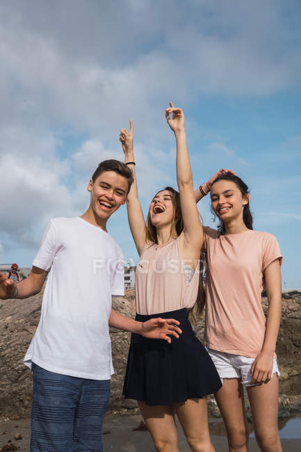 Portrait of smiling teenagers having fun on seashore in summer — Stock Photo