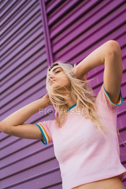 Молода жінка з фіолетовим навушники, стоячи з фіолетовим стіною — стокове фото