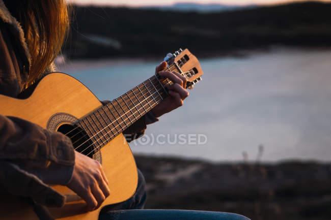 Nahaufnahme einer Frau, die in der Natur sitzt und Gitarre spielt — Stockfoto