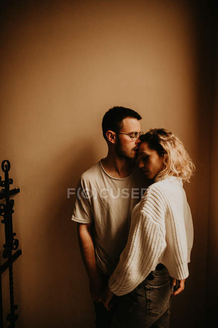 Romantic couple embracing in front of wall at home — Stock Photo