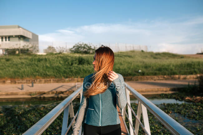 Portrait of attractive sporty young woman standing on pier in nature — Stock Photo