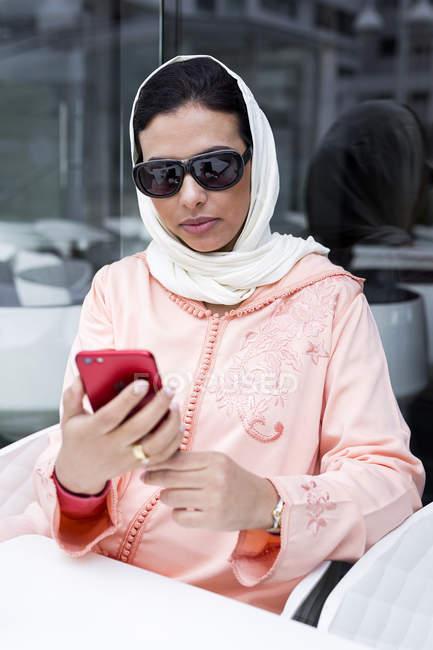 Marokkanerin mit Hijab und traditionelle arabische Kleidung mit Handy im café — Stockfoto