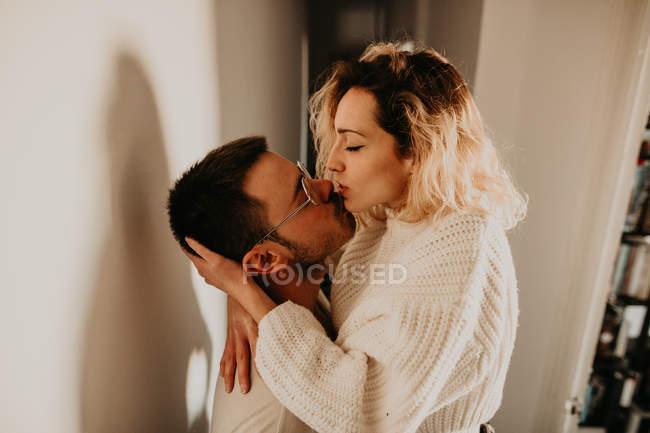 Leidenschaftliches Paar umarmt und küsst sich zu Hause an der Wand — Stockfoto