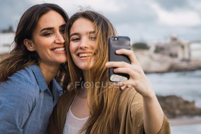 Femme souriante et adolescente prenant selfie au bord de mer — Photo de stock