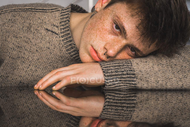 Emotionless handsome young man with freckles and piercing looking at camera while lying on hand on table — Stock Photo