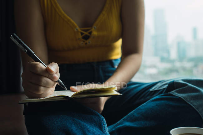 Close-up of female hand writing in notebook with pen — Stock Photo
