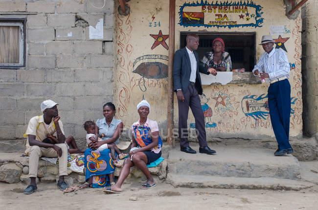 Ангола - Африка - 5 квітня 2018 - Африканський чоловіки і жінки стоять біля села магазин вікна на вулиці міста — стокове фото