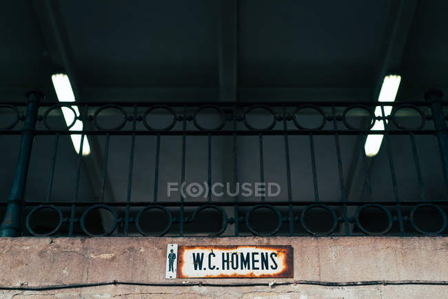 WC sign hanging on wall and black metal handrail — Stock Photo