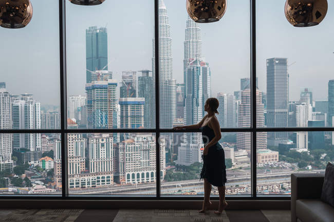 Woman standing at window in apartment and looking at skyscrapers — Stock Photo