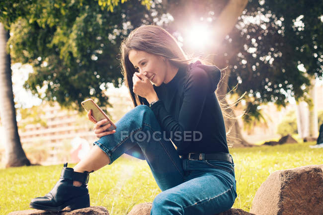 Young laughing woman sitting on rock and using smartphone in park — Stock Photo