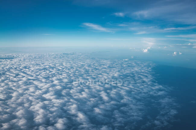 Endless view of white clouds below clear blue sky on huge height in sunlight — Stock Photo