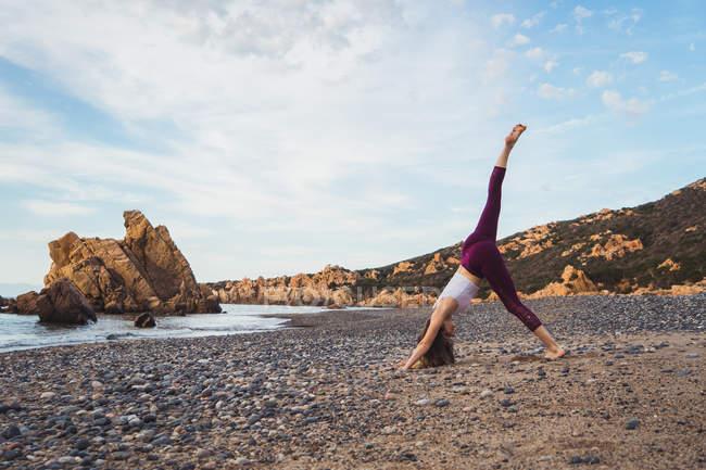 Спортивная женщина, стоящая с поднятой ногой и практикующая йогу на берегу океана — стоковое фото