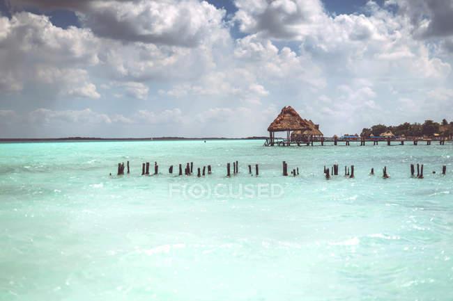 Lignes de piquets pourrissants dans la mer des Caraïbes turquoise avec ciel nuageux en arrière-plan, Mexique — Photo de stock