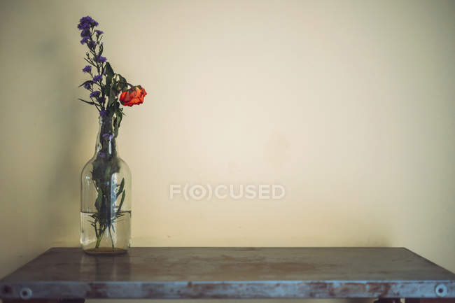 Vase with flowers on table in front of wall — Stock Photo