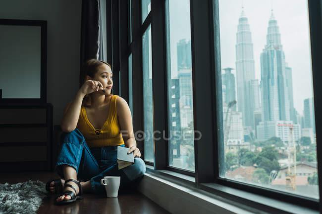 Donna con tazza e taccuino seduta sul pavimento alla finestra — Foto stock