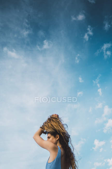Cheerful woman in blue swimsuit standing against blue sky — Stock Photo