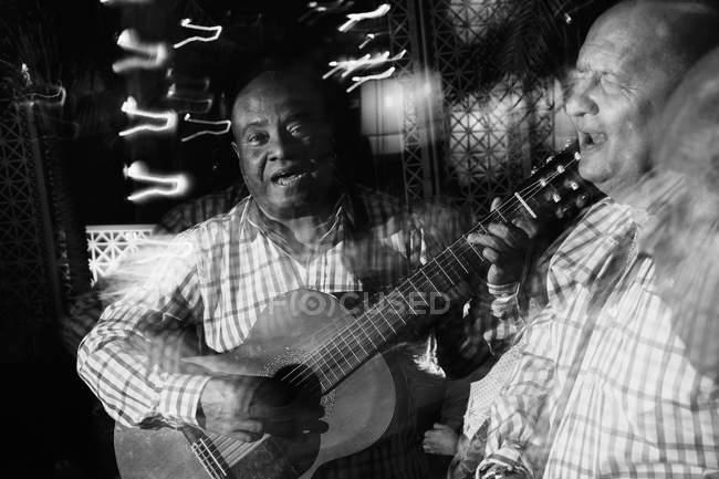 Trio musicale cubano che recita in night club, ripresa in bianco e nero con lunga esposizione — Foto stock