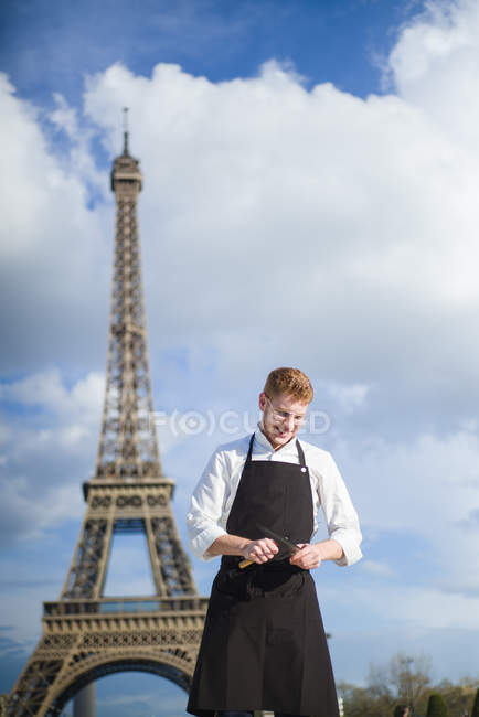 Smiling Red-Hair cook with knives standing in front of Eiffel Tower in Paris — Stock Photo