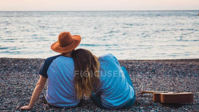 Чоловік і жінка сидить з гітарою на пляжі на березі моря — стокове фото