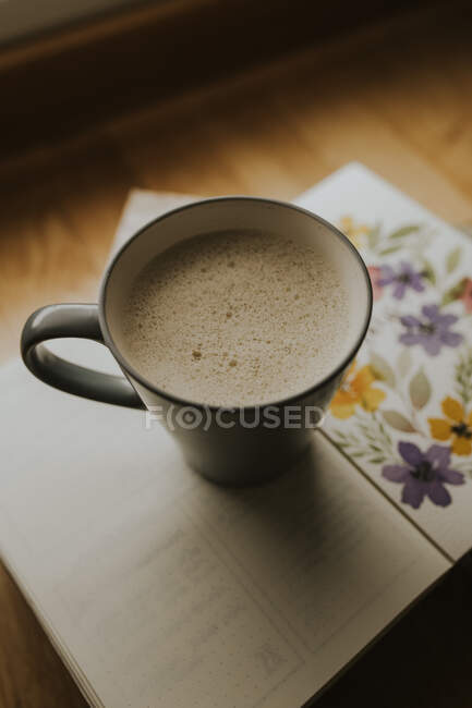 Cup of warm drink on book — Stock Photo