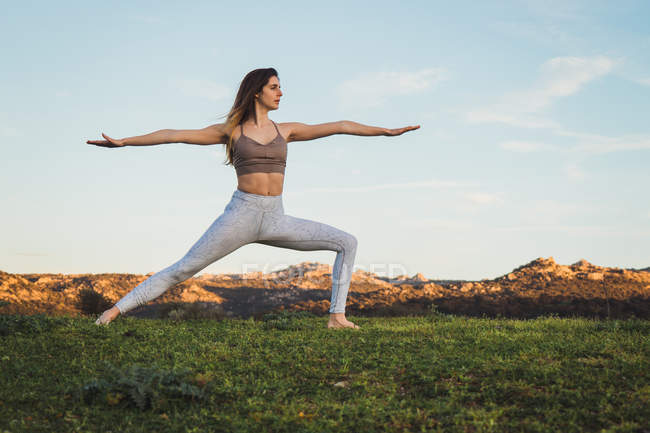 Fit woman doing yoga on green lawn with mountains on background — Stock Photo