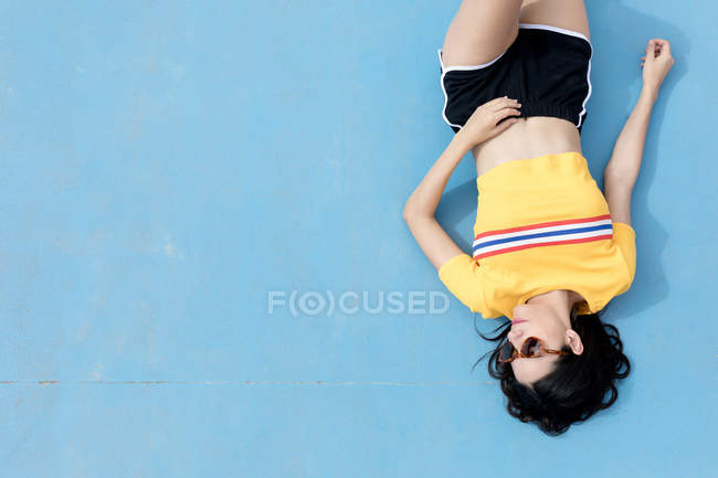 Woman in sportswear and sunglasses lying on blue background — Stock Photo