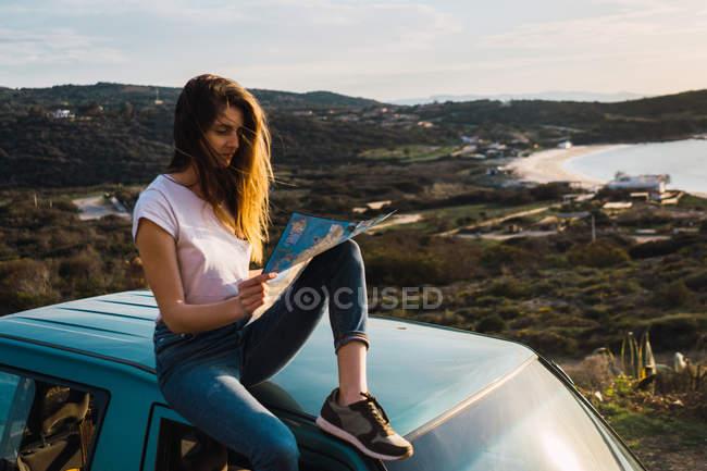 Женщина с картой на крыше автомобиля на побережье — стоковое фото