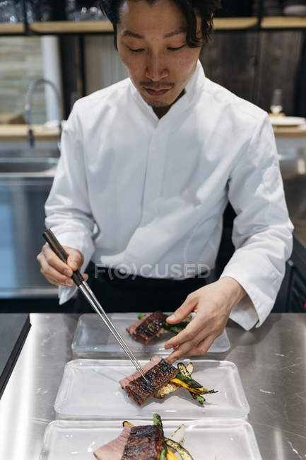Chef preparing dishes with chopsticks in restaurant — Stock Photo