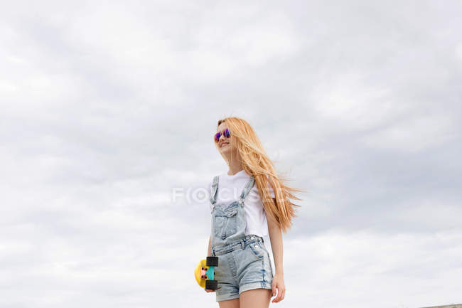 Blonde girl standing with penny board in front of cloudy sky — Stock Photo