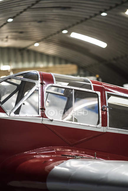Red carcass of small vintage airplane in hangar — Stock Photo