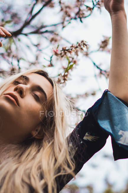 Молодая блондинка с закрытыми глазами стоит у цветущего дерева — стоковое фото