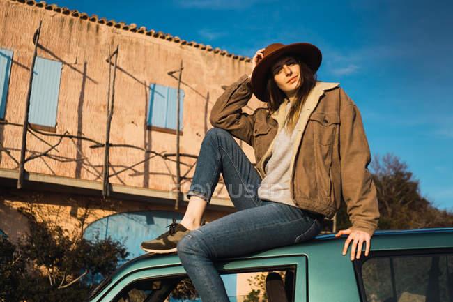 Bella donna turistica in cappello seduta sul tetto dell'auto di fronte all'edificio — Foto stock