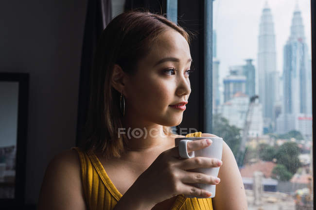 Riflessivo asiatico donna con coppa guardando attraverso finestra — Foto stock
