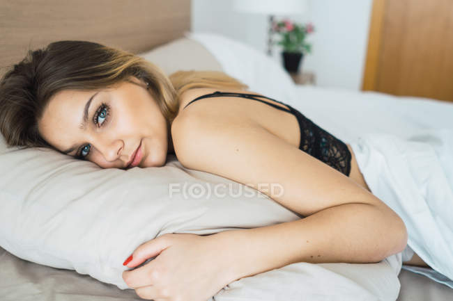 Young woman in black bra lying on bed and embracing pillow — Stock Photo