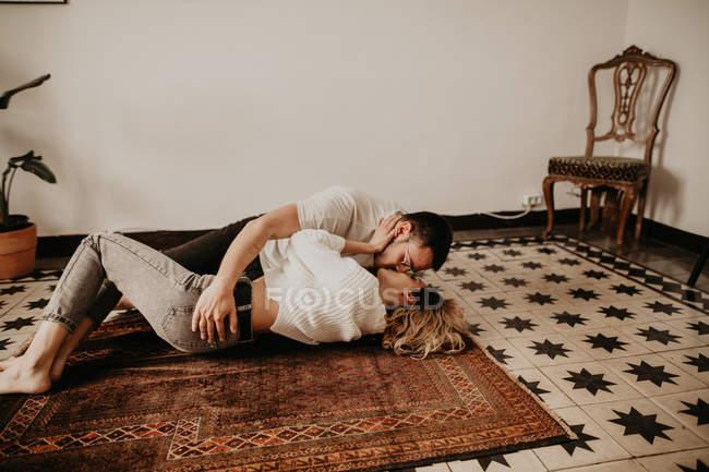 Couple affectueux gisant sur le sol et baiser à la maison — Photo de stock