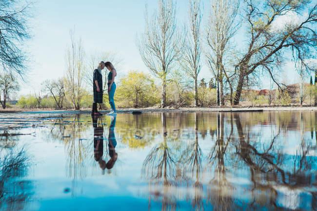 Filles debout tête à tête et réfléchissante dans immense flaque d'eau dans le parc du printemps — Photo de stock