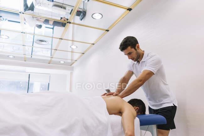 Фізіотерапевт лікує чоловіка за допомогою апаратури для радіотерапії. — стокове фото