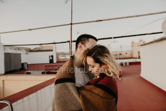 Пара обнимается с одеялом на террасе — стоковое фото