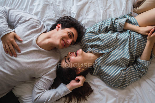 Happy young couple lying on bed and smiling — Stock Photo