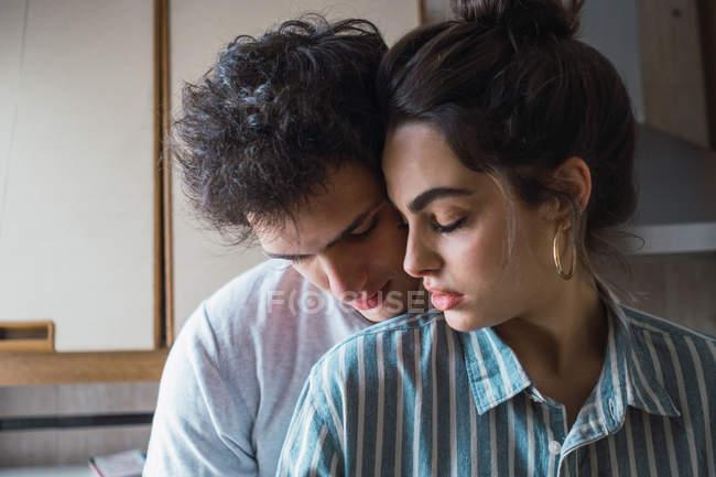 Sinnliches junges Paar steht und umarmt zu Hause in der Küche — Stockfoto